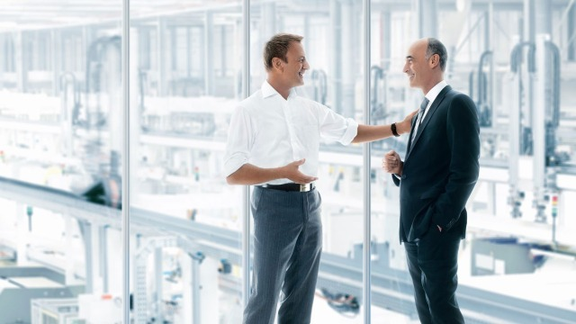 Two men, one in a white shirt, one in a suit, talking. A production facility can be seen in the background.