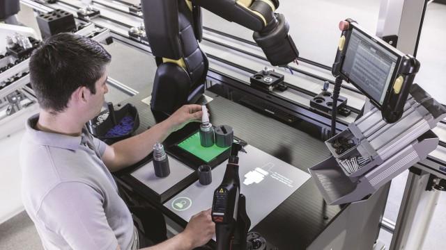 Ein Cobot und ein Mann arbeiten gemeinsam an einer automatisierten Montagelinie.