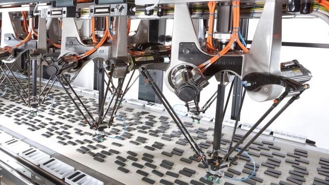 Ein kartesischer Dreiarm-Roboter (oder Tripod) greift Schokoladenkekse und sortiert sie in ihre Verpackung.
