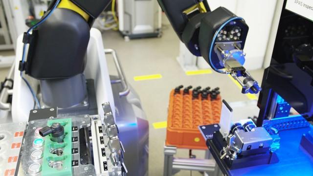 Ein Roboter inspiziert visuell Bauteile aus einer automatisierten Montagelinie.