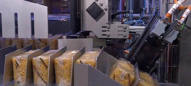 Mehrere Päckchen mit Nudeln in einer Kunststoffverpackung werden durch eine Verpackungsmaschine befördert.