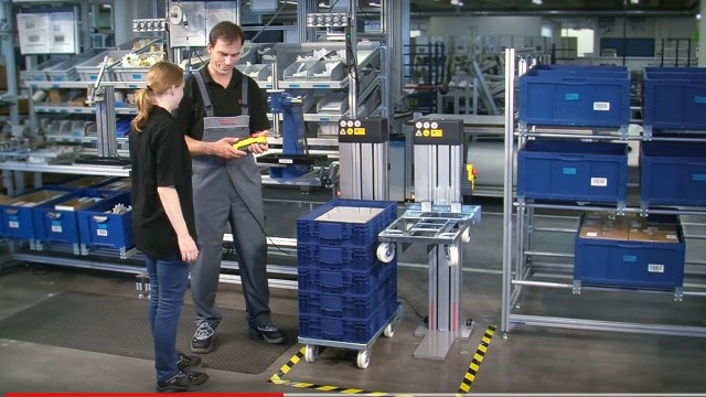 Mitarbeiter bedienen ein Kistenhubgerät von BoschRexroth